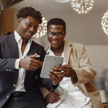Black men in a cafe. Guy talking. Man in a black suit. Friends use the tablet.